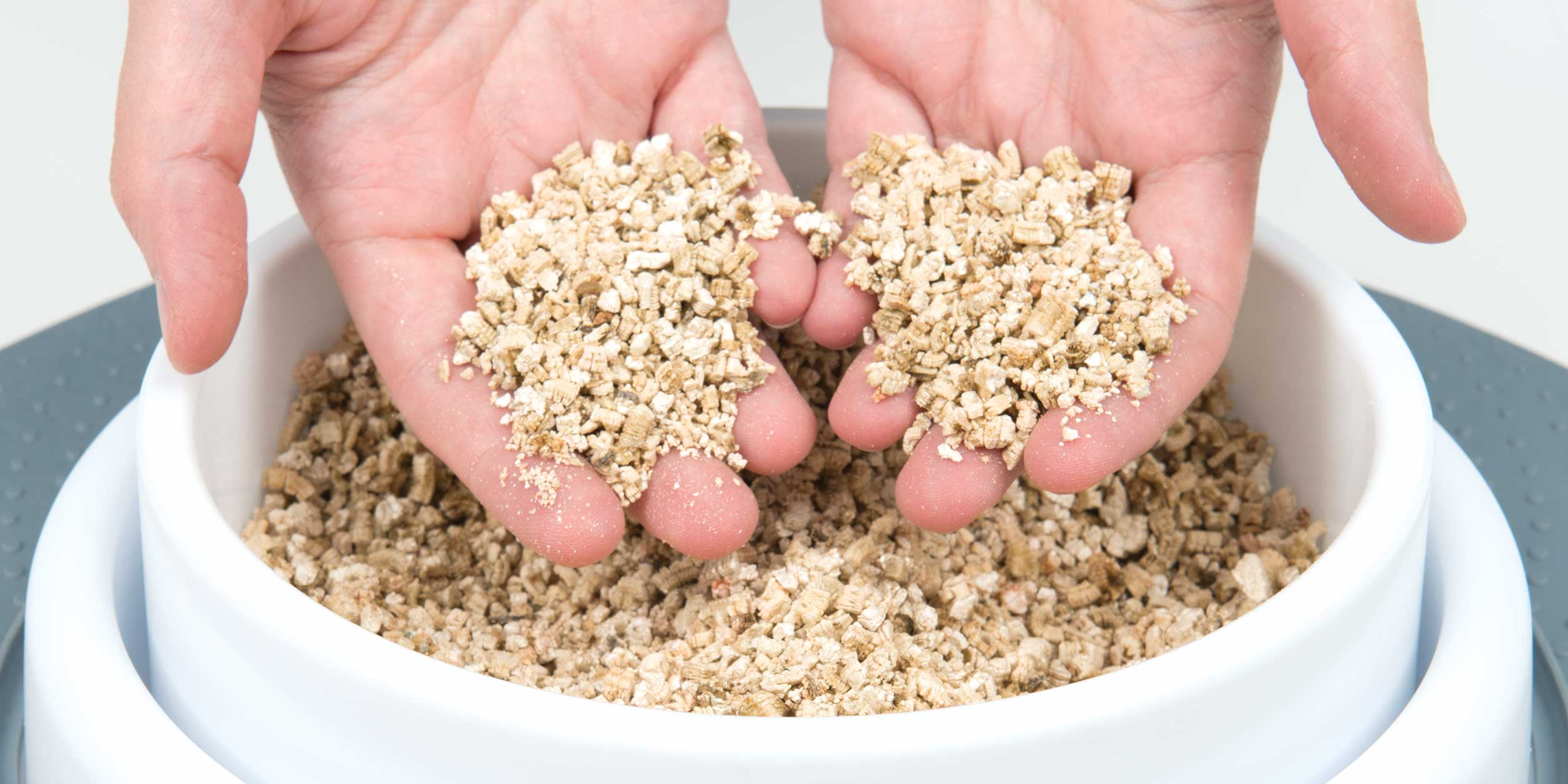 Clean hands holding the vermiculite in the Senses 2.0 Grass Planter