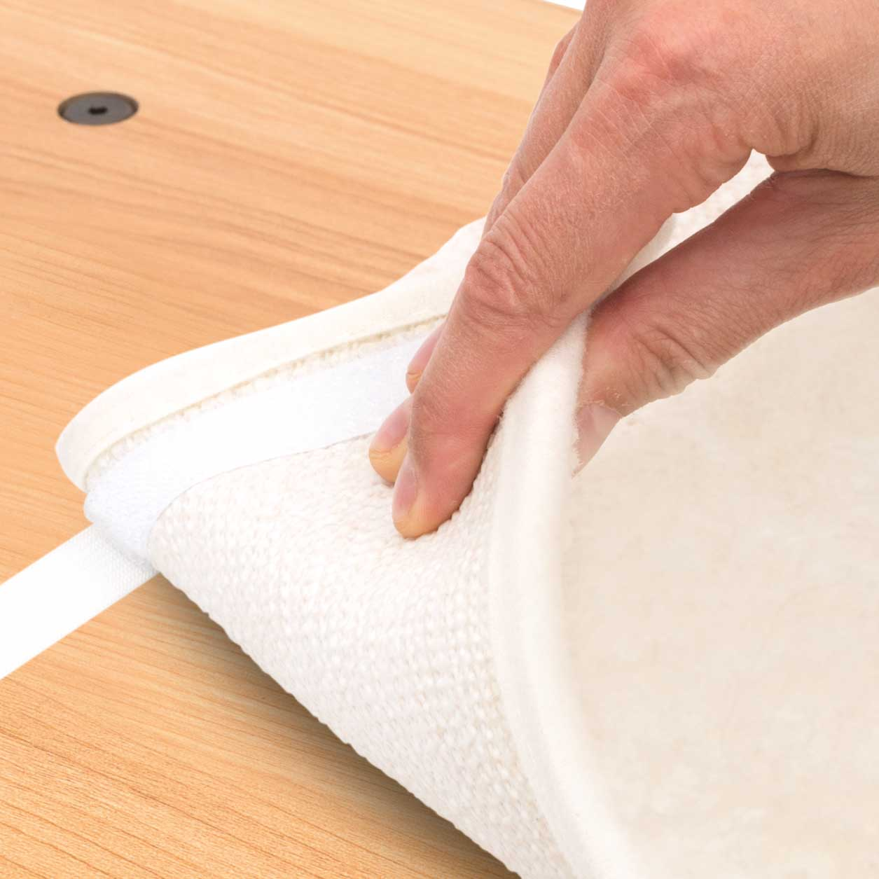 Hand unhooking cushion from a Vesper cat furniture